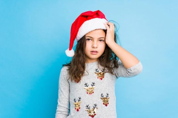 Niña celebrando el día de navidad cansado y con mucho sueño manteniendo la mano en la cabeza.