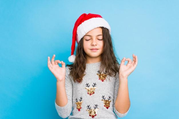 Niña celebrando el día de navidad se relaja después de un duro día de trabajo, ella está realizando yoga.