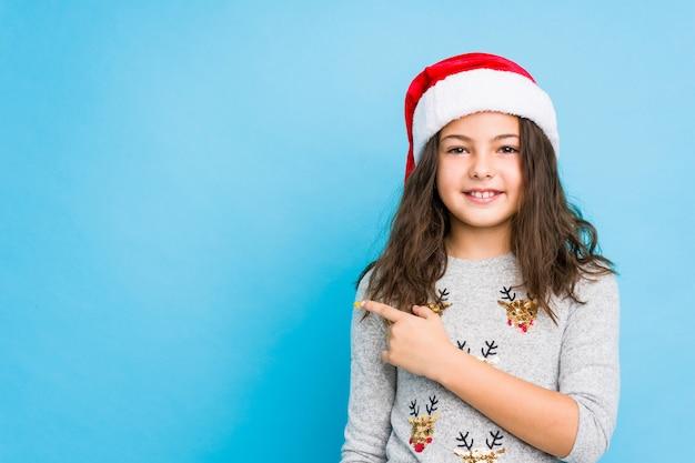Niña celebrando el día de navidad sonriendo y señalando a un lado, mostrando algo en el espacio en blanco.