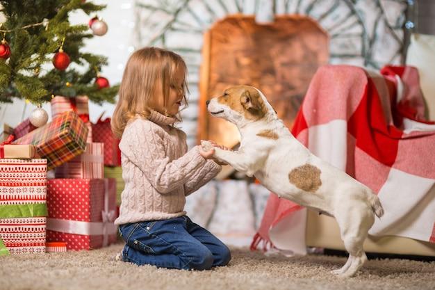 Niña celebrando una feliz navidad en casa junto a la chimenea con un perro jack russell