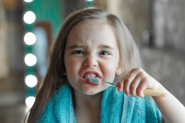 Una niña se cepilla los dientes en el baño. retrato de un niño con un cepillo de dientes