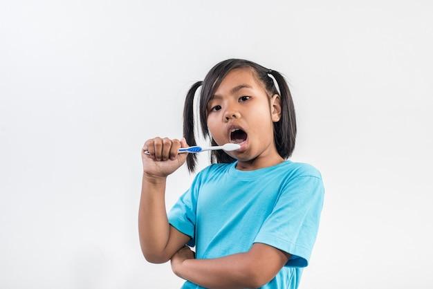 Niña cepillando sus dientes en tiro del estudio