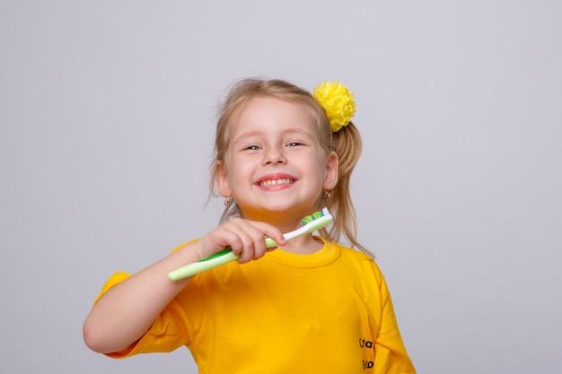 Niña con un cepillo de dientes, niña con un cepillo de dientes y una manzana.