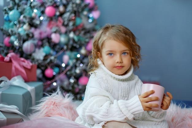 Una niña cerca del árbol de navidad sostiene una taza de té caliente