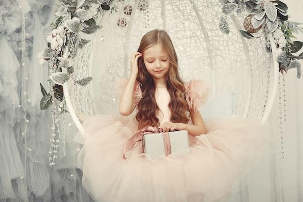 Niña cerca del árbol de navidad en un vestido rosa