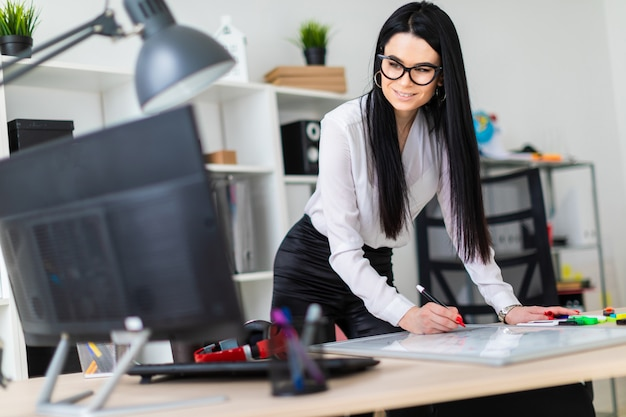 Una niña está cerca de un escritorio de computadora y dibuja un marcador en una pizarra magnética.