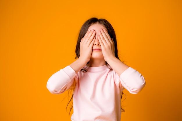 La niña cerró los ojos y las orejas con las manos.