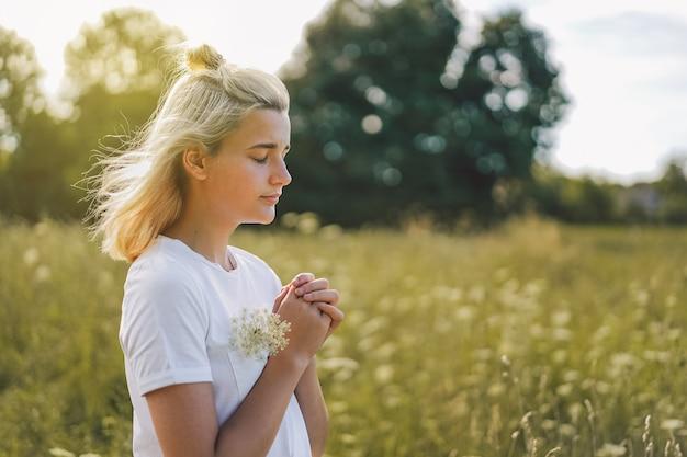 Niña cerró los ojos, rezando en un campo. manos juntas en concepto de oración por fe