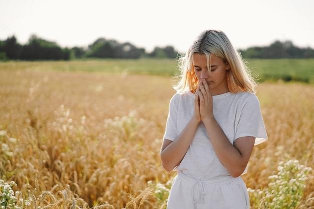Niña cerró los ojos, rezando en un campo. manos juntas en concepto de oración por la fe.