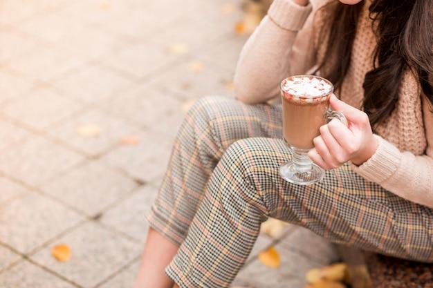 Una niña con una chaqueta beige y pantalones en una jaula se sienta en la calle y posa con un vaso de chocolate caliente en las manos. foto