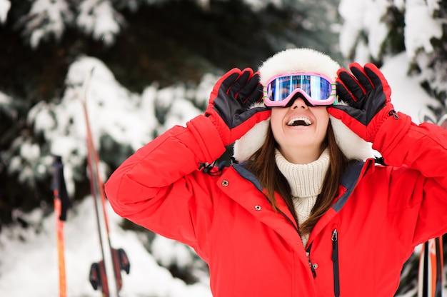 Niña en una chaqueta deportiva roja en el bosque de invierno de esquí,