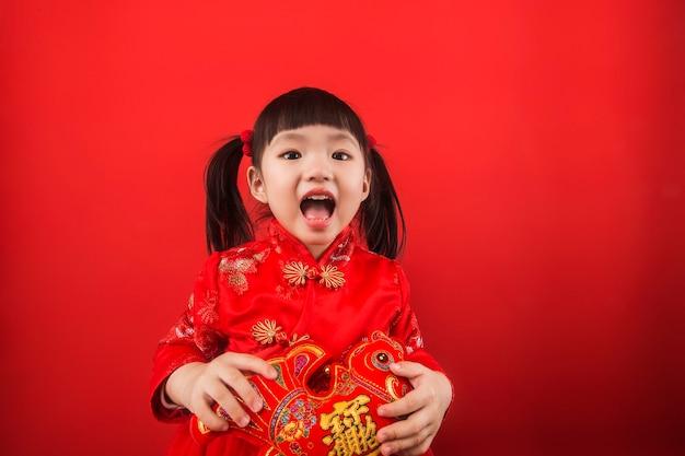 Una niña china celebra la fiesta de la primavera con lingotes de oro. traducción china de lingotes de oro: riqueza de lingotes de oro