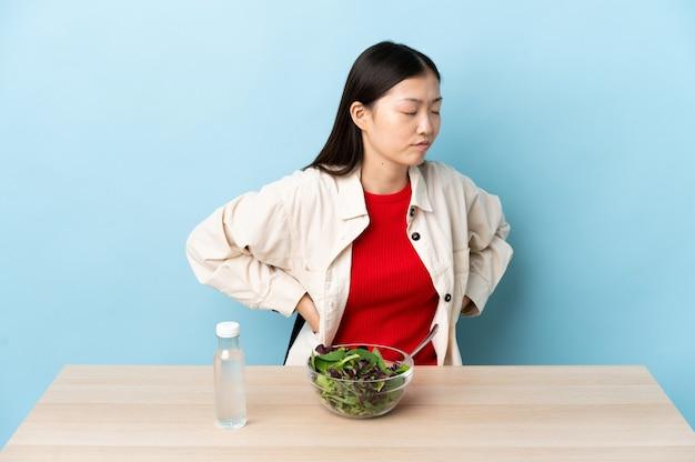 Niña china comiendo una ensalada sufre de dolor de espalda por haber hecho un esfuerzo