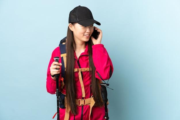 Niña china con mochila y bastones de trekking sobre azul aislado manteniendo una conversación con el teléfono móvil con alguien