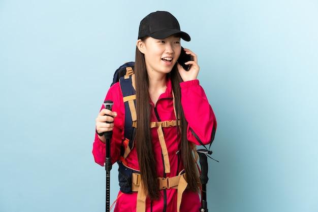 Niña china con mochila y bastones de trekking sobre azul aislado manteniendo una conversación con el teléfono móvil