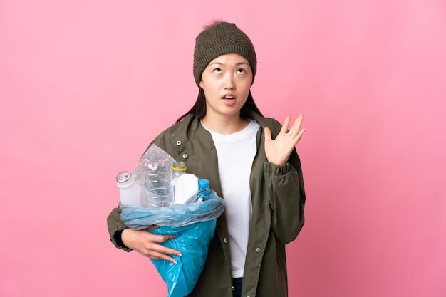 Niña china sosteniendo una bolsa llena de botellas de plástico para reciclar en rosa aislado estresado en
