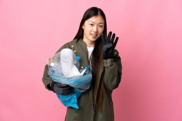 Niña china sosteniendo una bolsa llena de botellas de plástico para reciclar en rosa feliz aislado y contando cuatro con los dedos