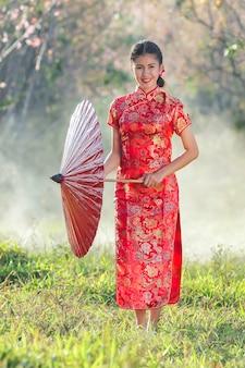 Niña china con vestido tradicional cheongsam en jardín