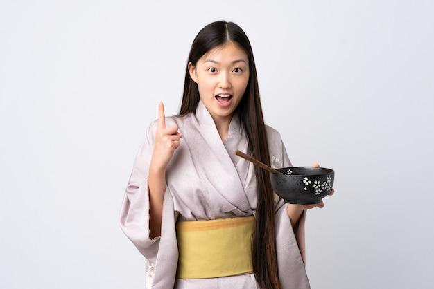 Niña china vistiendo kimono sobre pared blanca aislada apuntando hacia una gran idea mientras sostiene un plato de fideos con palillos