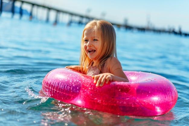 Niña con círculo inflable rosa bañándose en el mar