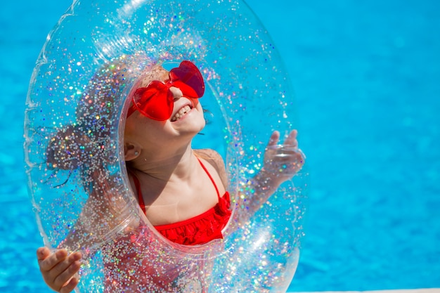 Niña con un círculo de natación en la piscina