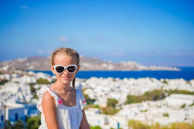 Niña en la ciudad europea al aire libre en la isla de mykonos