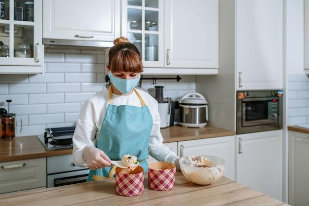 Niña cocinera con una máscara médica y guantes, colocando la masa en moldes para pasteles de pascua