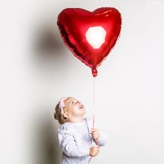 Niña coge un globo de aire de corazón sobre un fondo claro. concepto para el día de san valentín, cumpleaños. bandera.