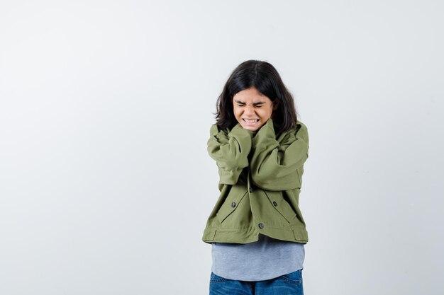 Niña cogidos de la mano en el cuello en abrigo, camiseta, jeans y mirando confundido, vista frontal.