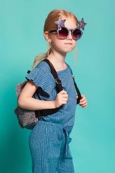 Niña con una cola en ropa elegante y gafas de sol sobre fondo azul