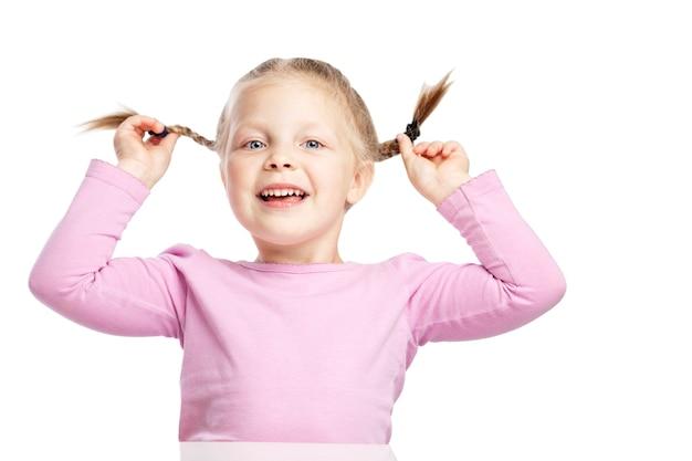 Niña con coletas en un suéter rosa se está riendo.