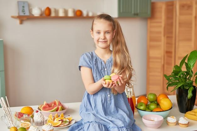 Niña come dulces macarons en la cocina