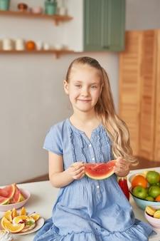 Niña come fruta en la cocina