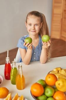 Niña come fruta en una mesa llena de comida