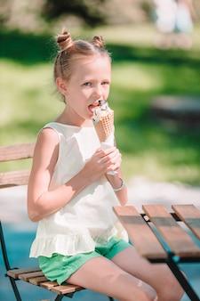 Niña comiendo helado al aire libre en verano en un café al aire libre