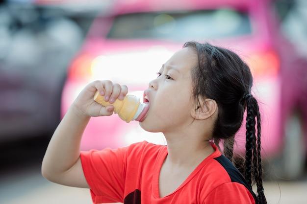 La niña está comiendo helado en el estacionamiento al aire libre.