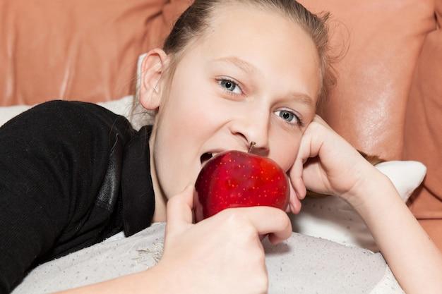 Niña comiendo una manzana roja