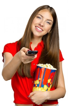 Niña comiendo palomitas de maíz y viendo televisión