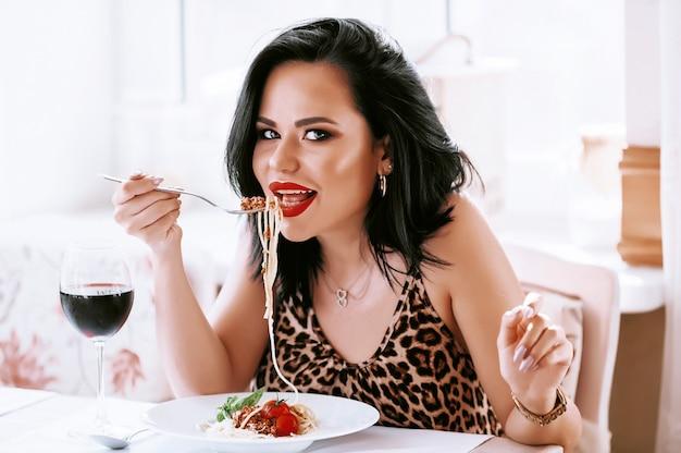 Niña comiendo pasta en un restaurante lavando su vino tinto
