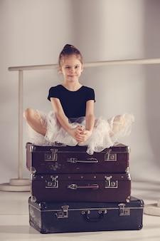 La niña como bailarina de balerina sentada en el estudio