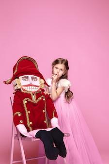 Una niña como bailarina de belleza en vestido largo rosa con cascanueces en estudio rosa