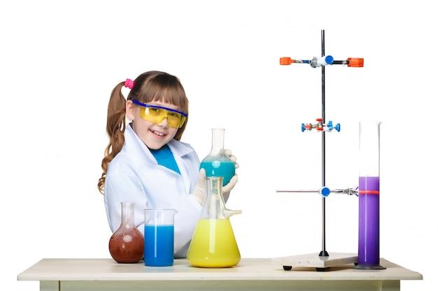 Niña como químico haciendo experimento con fluido químico en el laboratorio