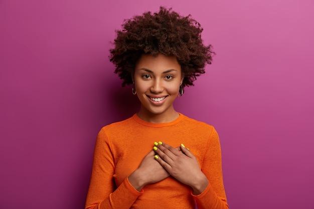 La niña complacida con un jersey naranja presiona las palmas contra el corazón, hace un gesto de agradecimiento, conmovida con felicitaciones cordiales, sonríe positivamente, aislada sobre la pared púrpura. concepto de reconocimiento