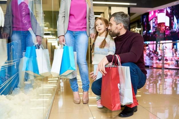 Niña de compras con padres
