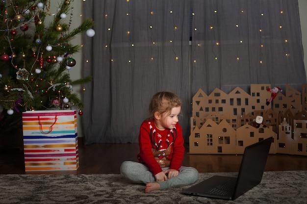 Una niña y una computadora portátil en el árbol de navidad con un libro en navidad. un niño y una computadora para el año nuevo.