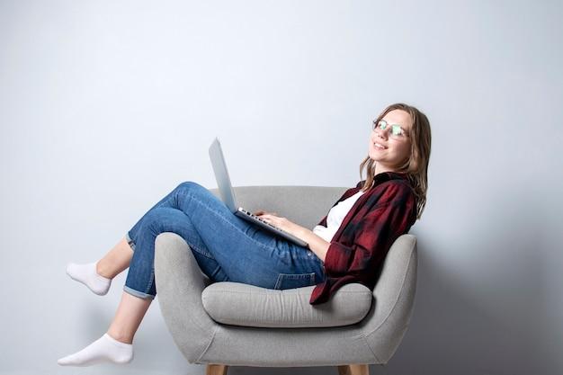 Niña con una computadora portátil sentada en una silla suave y cómoda, y sonriendo, una mujer usando una computadora contra una pared blanca en blanco, ella trabaja independientemente e imprime texto, copia espacio