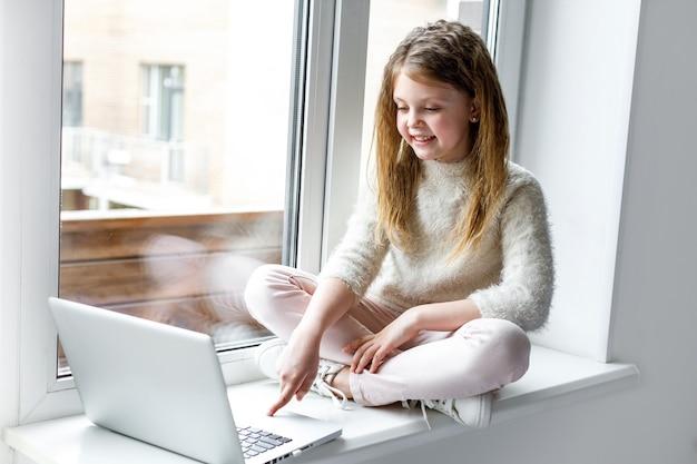 Una niña con una computadora portátil se sienta en casa en el alféizar de la ventana