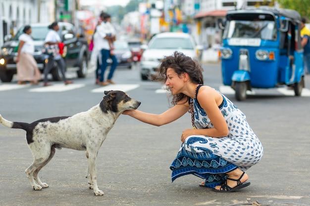 La niña se comunica con un perro callejero en la calle. acaricia el perro.