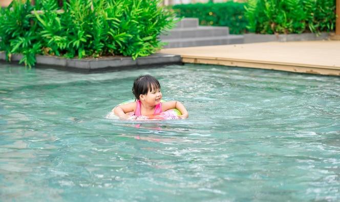 Niña con anillo de goma en la piscina