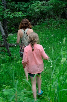 Niña con su madre caminando en un bosque, lago de los bosques, ontario, canadá